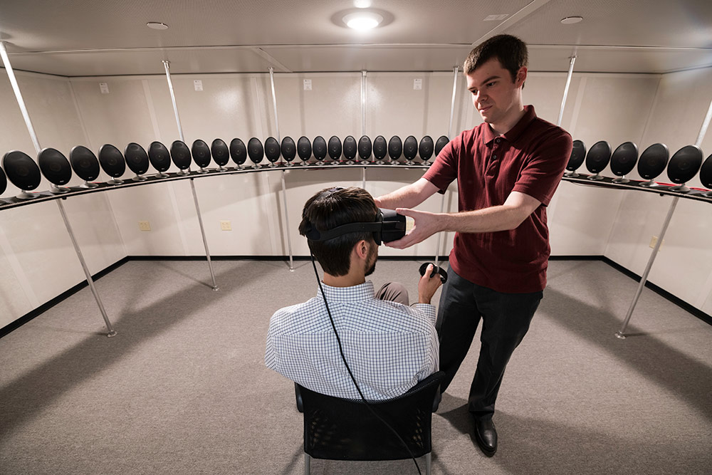 Biomedical engineering graduate student Tom Stoll, right, adjusts a virtual reality head-mounted display on assistant professor Ross Maddox. The array of speakers in Maddox's lab allows researchers to simulate realistic listening environments.